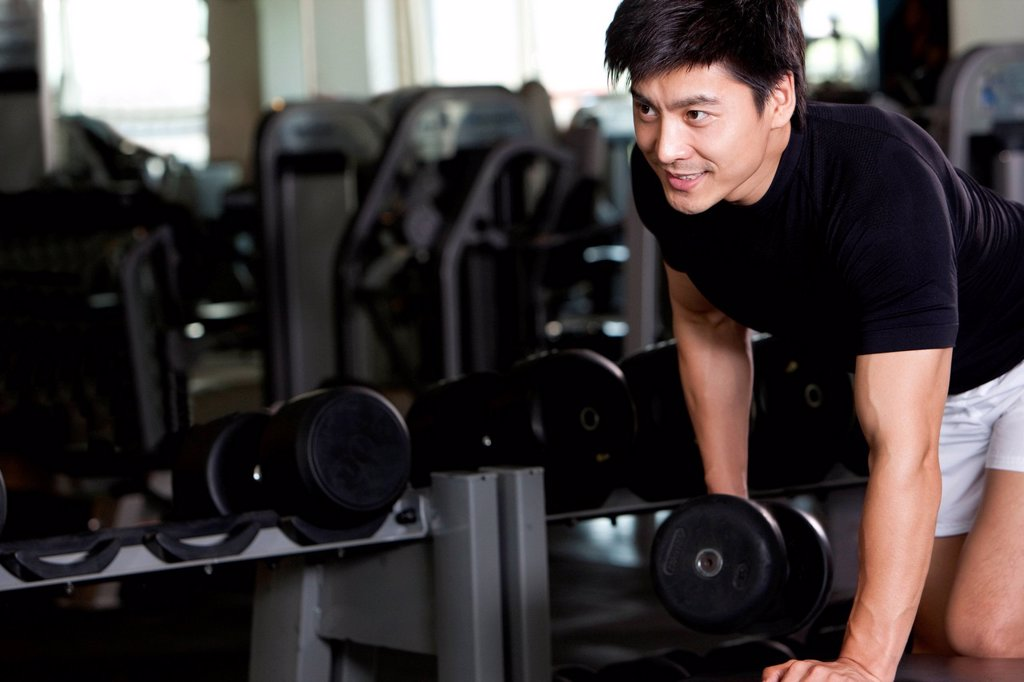 Stock Photo: 1839R-29149 Mid_Adult Man Lifting Weights