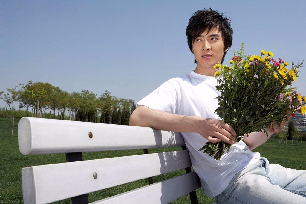 Stock Photo: 1839R-2939 Young Man Sitting On A Park Bench Holding Flowers