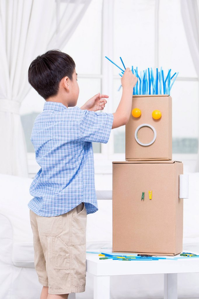 Boy making a toy robot : Stock Photo