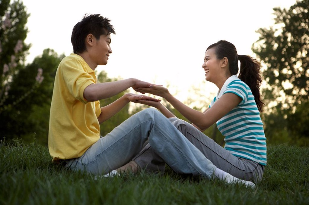 Young Couple Sitting In Park Together : Stock Photo