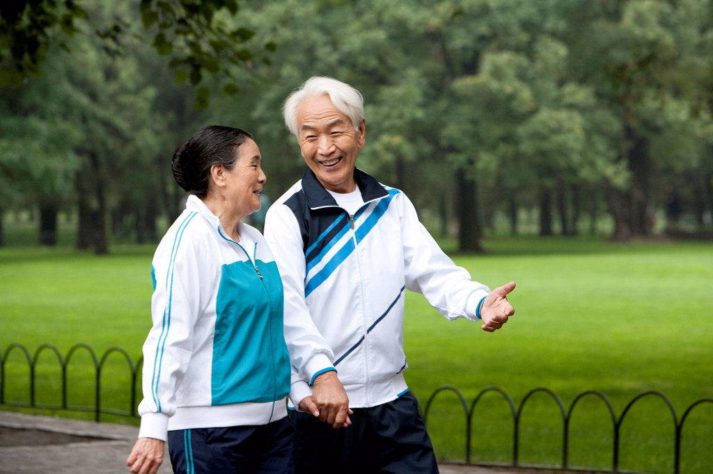 Stock Photo: 1839R-29730 Senior Couple Walking Hand_In_Hand Through a Park