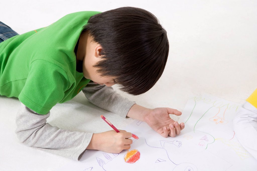 Stock Photo: 1839R-29787 A young boy coloring while lying on the floor