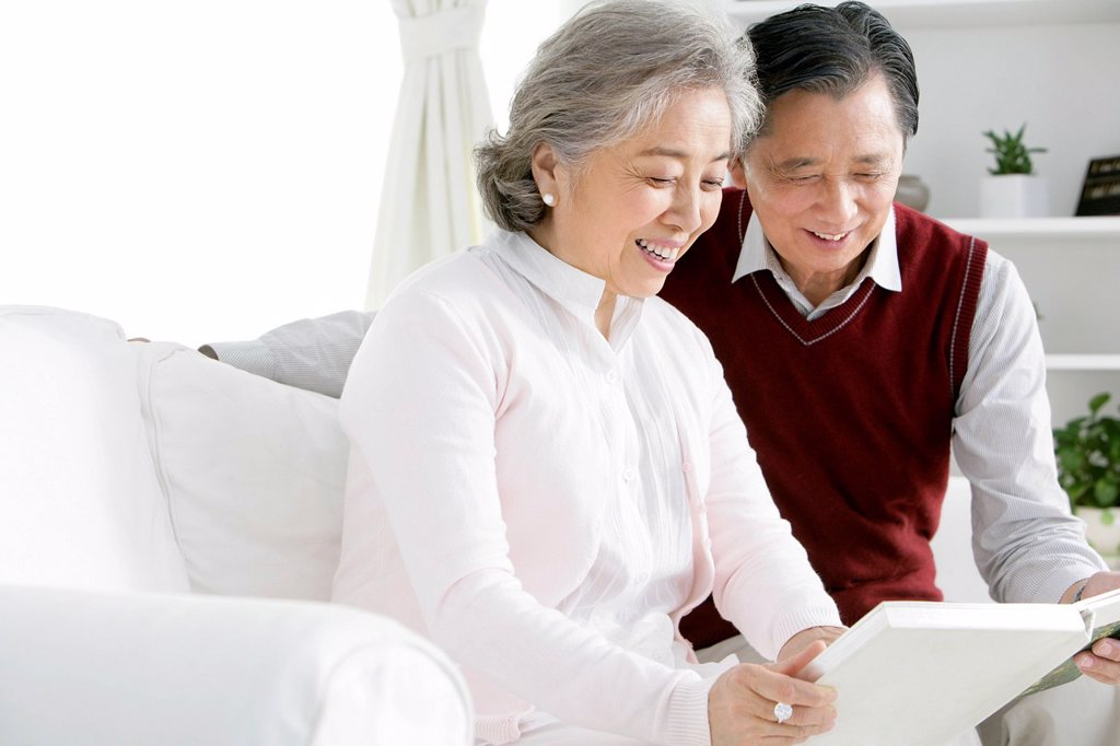 Senior Chinese couple looking at photo album : Stock Photo