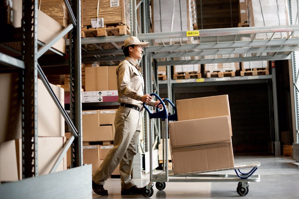 Stock Photo: 1839R-30113 Male Chinese warehouse worker pushing boxes