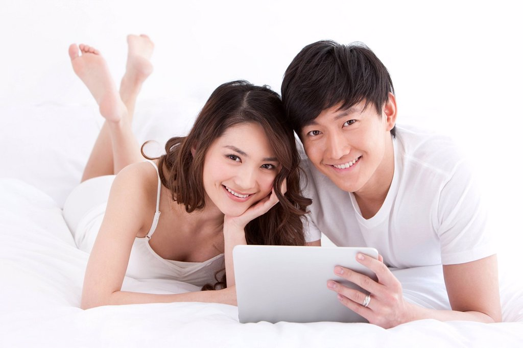 Young couple using digital tablet in bed : Stock Photo