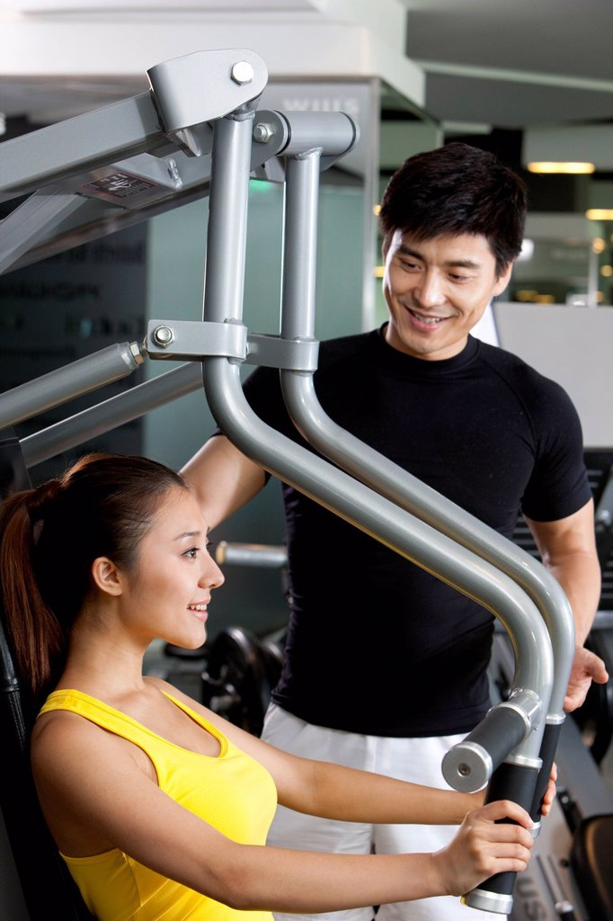 Trainer Helping Young Woman Use Exercise Machine : Stock Photo