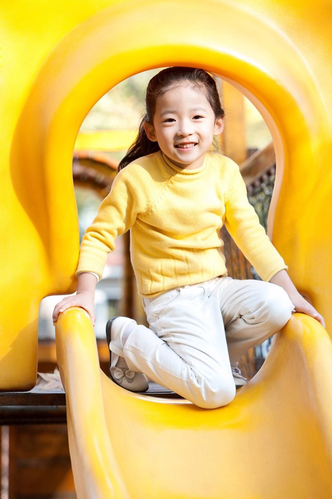 Stock Photo: 1839R-30929 Girl playing on playground slide