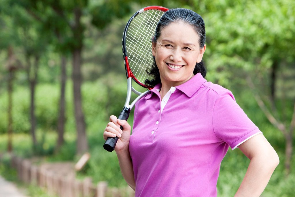 Stock Photo: 1839R-31154 Senior woman playing tennis in park