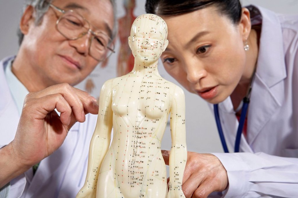 Doctor And Nurse Drawing On Human Acupuncture Figurine : Stock Photo