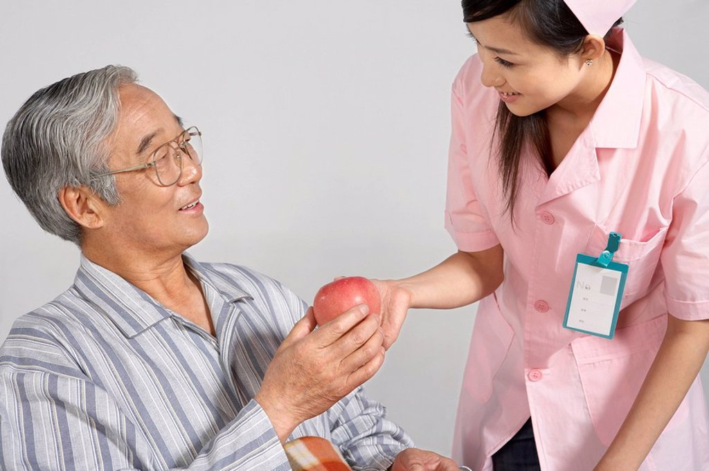 Stock Photo: 1839R-3143 Nurse Giving An Apple To Man