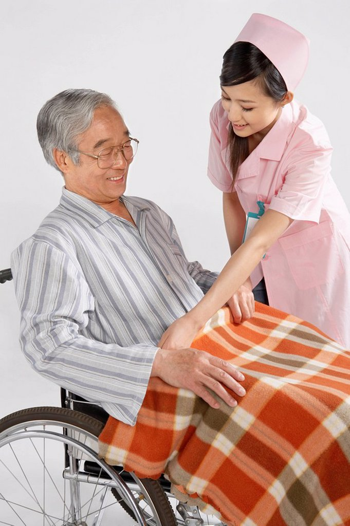 Nurse Fixing Blanket For Man In Wheelchair : Stock Photo