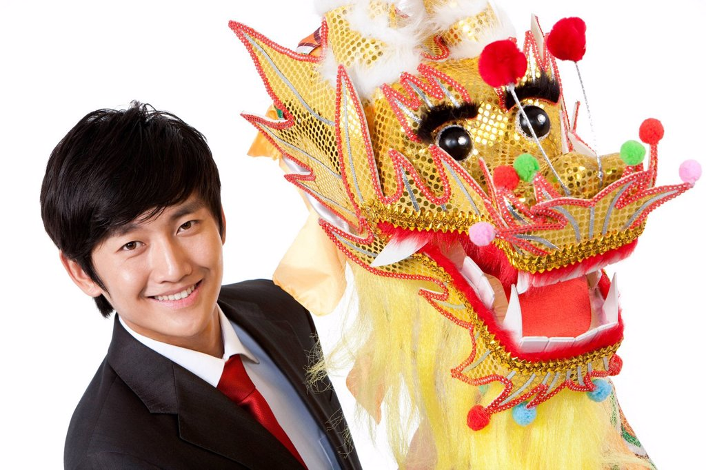 Businessman practising Chinese dragon dancing : Stock Photo