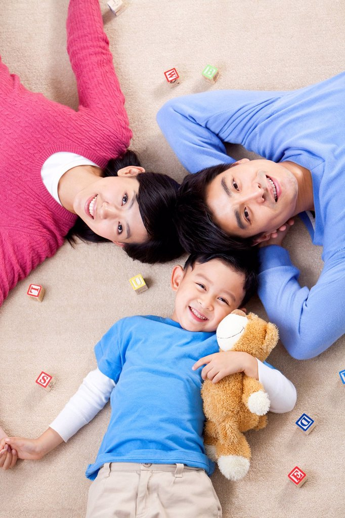 Young Chinese family lying on the floor : Stock Photo
