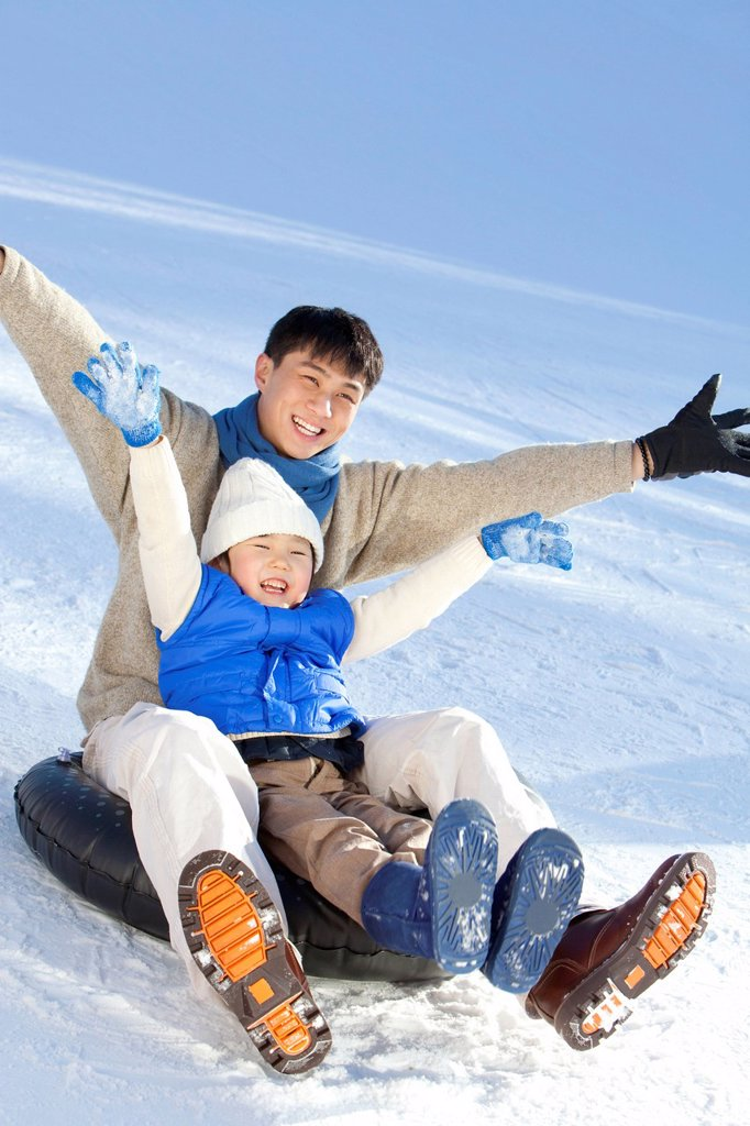 Stock Photo: 1839R-31879 Father playing with son in snow
