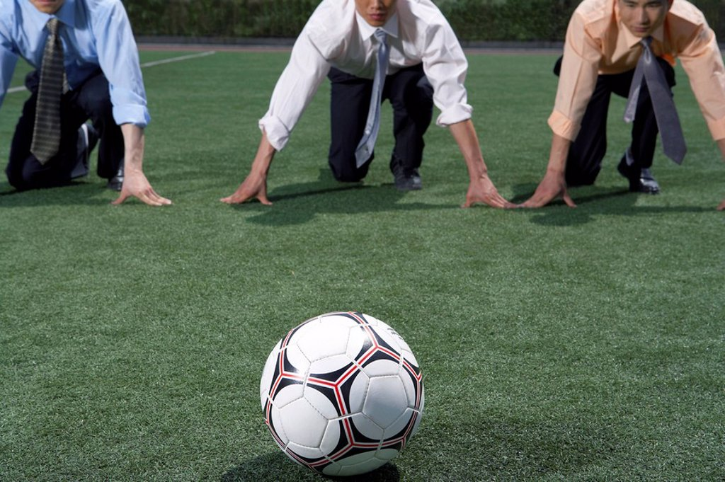 Stock Photo: 1839R-3216 Businessmen On A Field Preparing To Run To A Soccer Ball