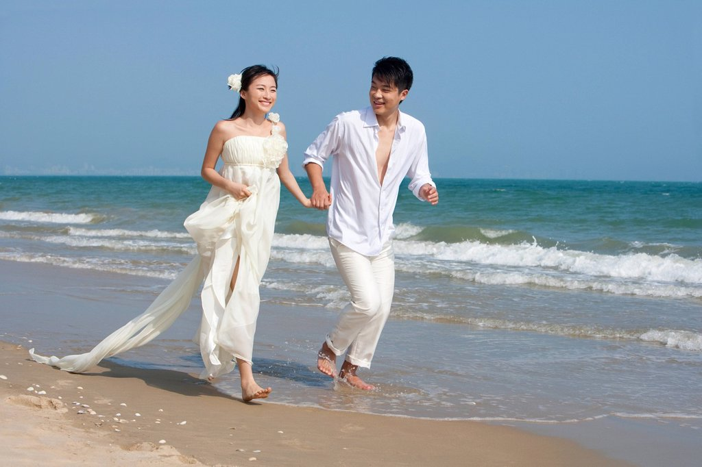 Stock Photo: 1839R-32212 Happy Newlyweds Running on the beach