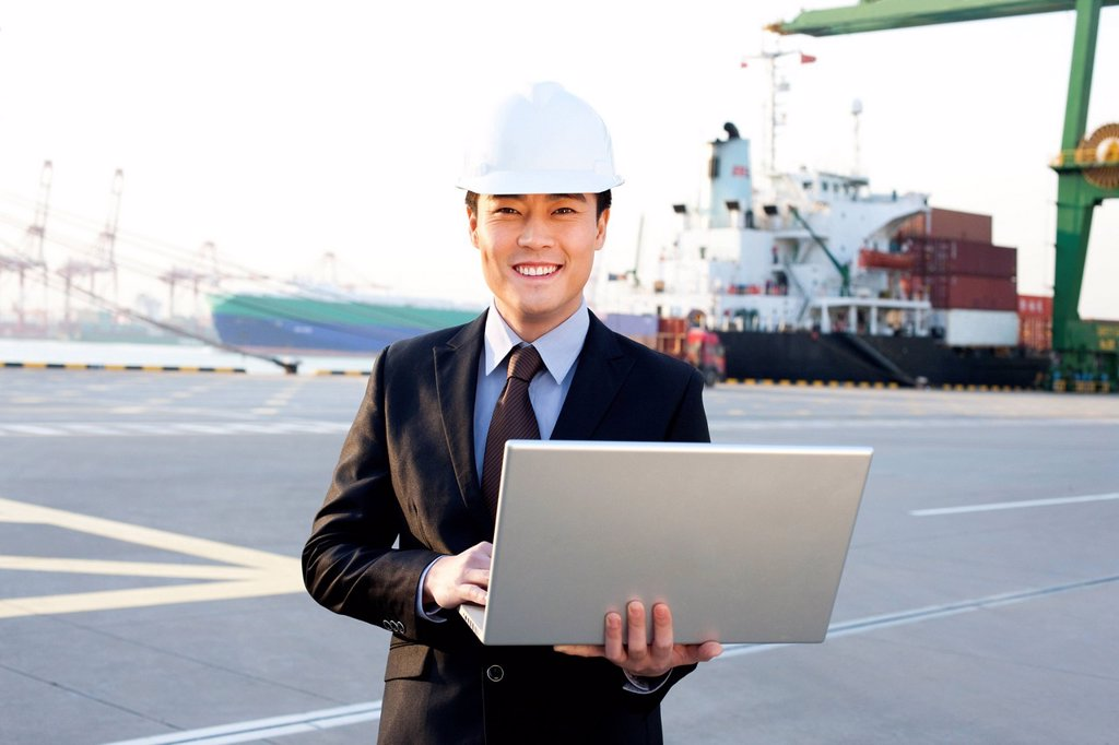Stock Photo: 1839R-32394 businessman using a laptop at a shipping port