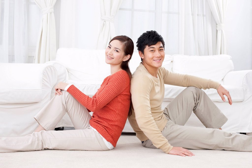 Stock Photo: 1839R-32399 Happy young couple sitting on carpet
