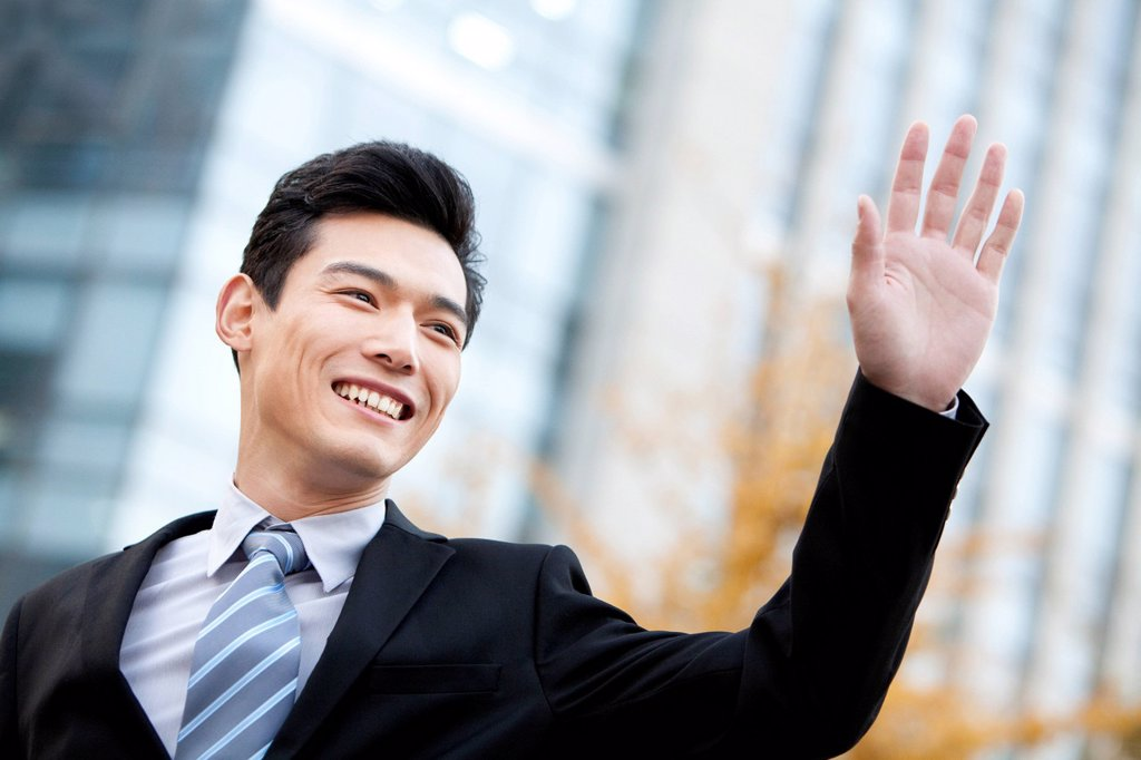 A businessman outside office buildings waving : Stock Photo