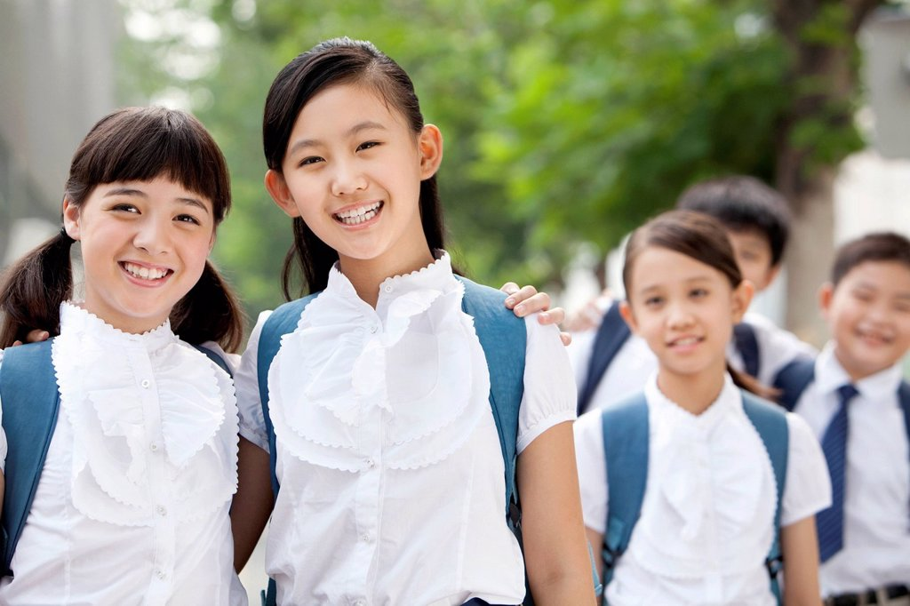 Stock Photo: 1839R-33119 Happy schoolgirls in uniform with friends outdoors