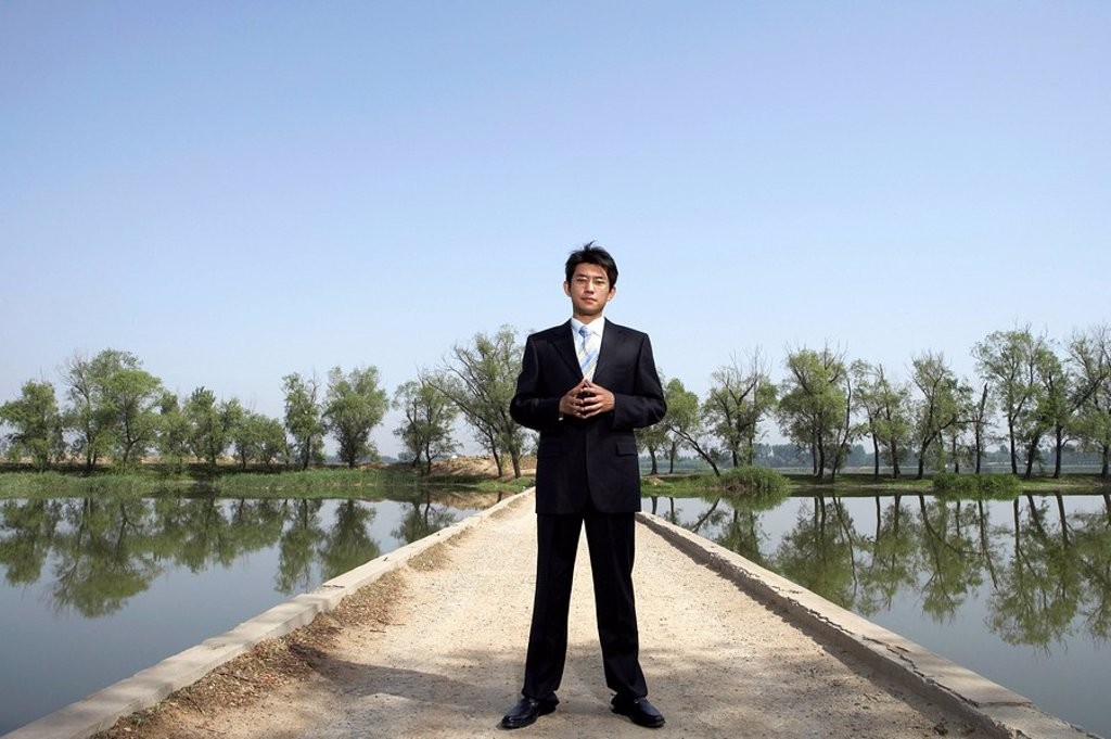 Stock Photo: 1839R-3341 Businessman Standing Next To A Lake On A Bridge