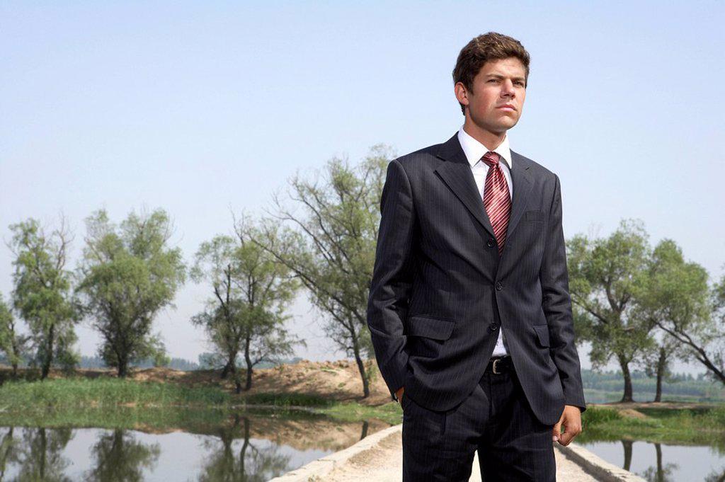 Businessman Standing Next To A Lake On A Bridge : Stock Photo