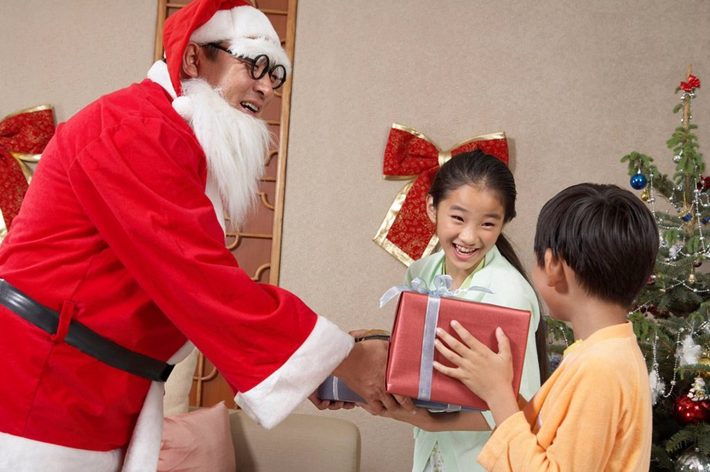 Stock Photo: 1839R-3463 Santa Giving Presents To Young Excited Children