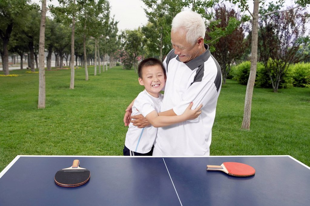Stock Photo: 1839R-3760 Grandfather And Grandson Playing Ping Pong