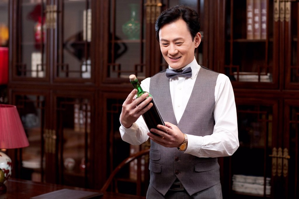 Stock Photo: 1839R-38157 Wealthy businessman with red wine bottle