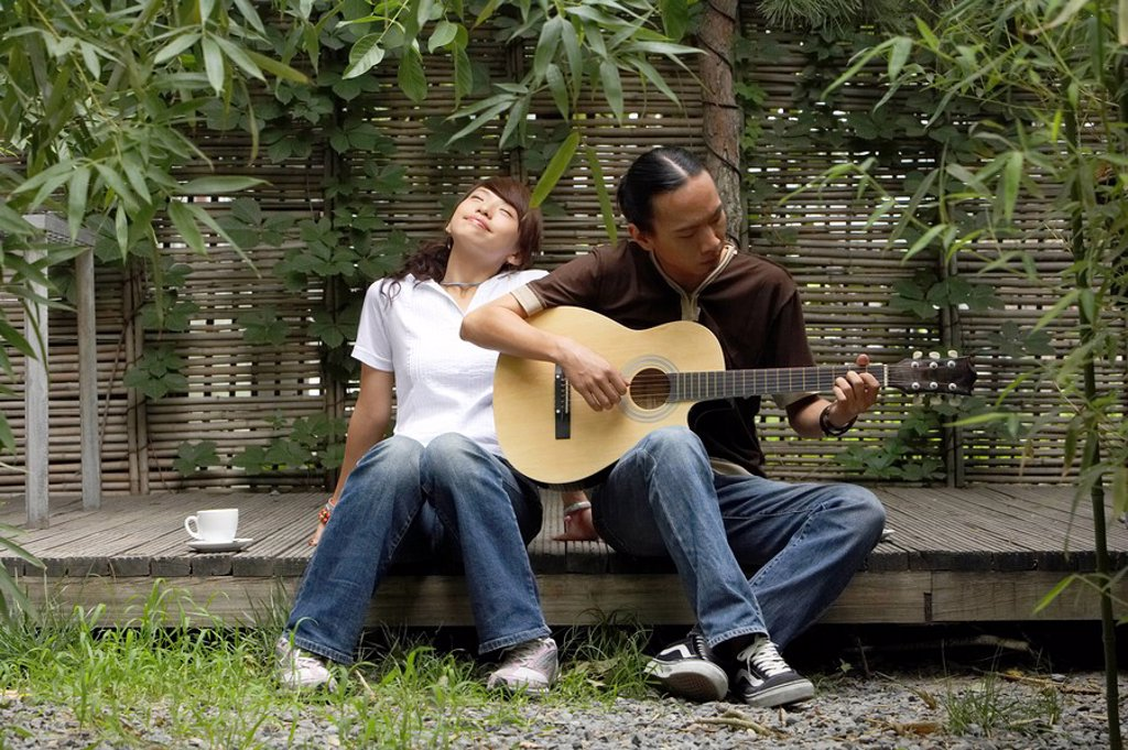 Young Man Playing Guitar While Young Woman Listens And Smiles : Stock Photo