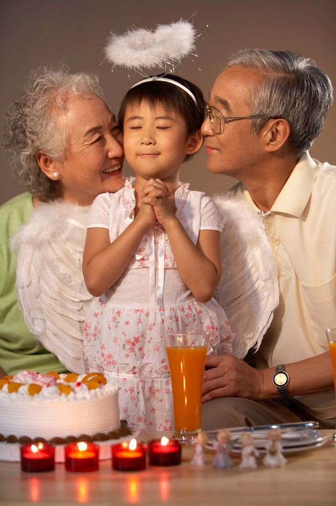Stock Photo: 1839R-3952 Grandparents Watch As Their Granddaughter Makes A Birthday Wish
