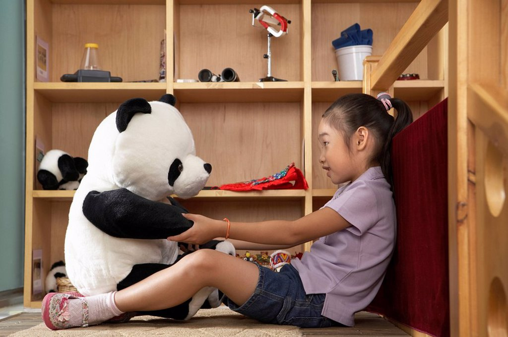 Young Girl Talking To A Stuffed Toy Panda : Stock Photo