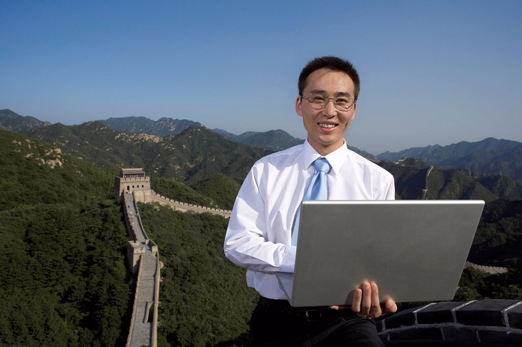Businessman Typing On Laptop Computer On The Great Wall Of China : Stock Photo