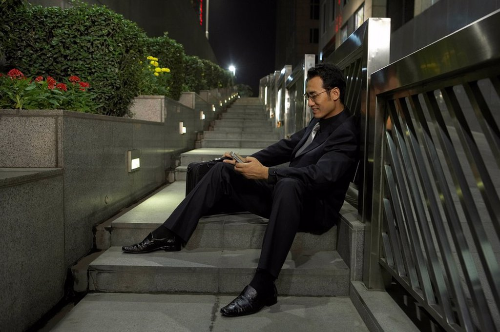 Stock Photo: 1839R-4431 Businessman Using Cellphone While Sitting On Steps