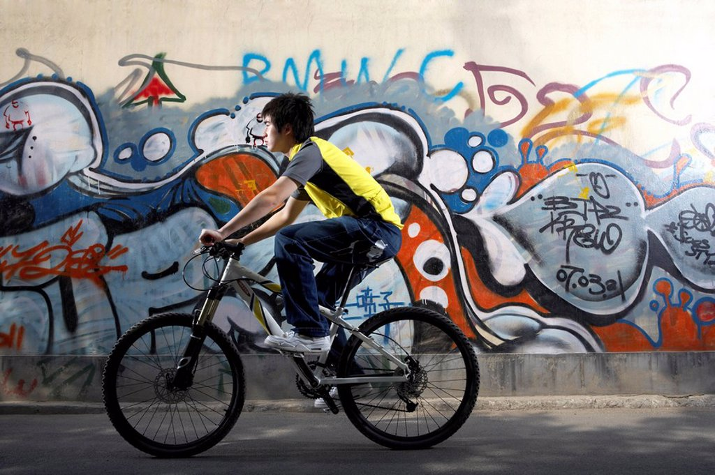 Teenage Boy Riding A Bike Past Graffiti : Stock Photo