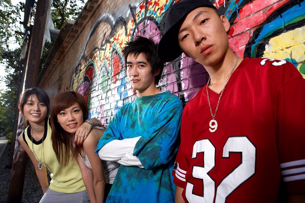 Teenagers Leaning On A Wall Of Graffiti : Stock Photo