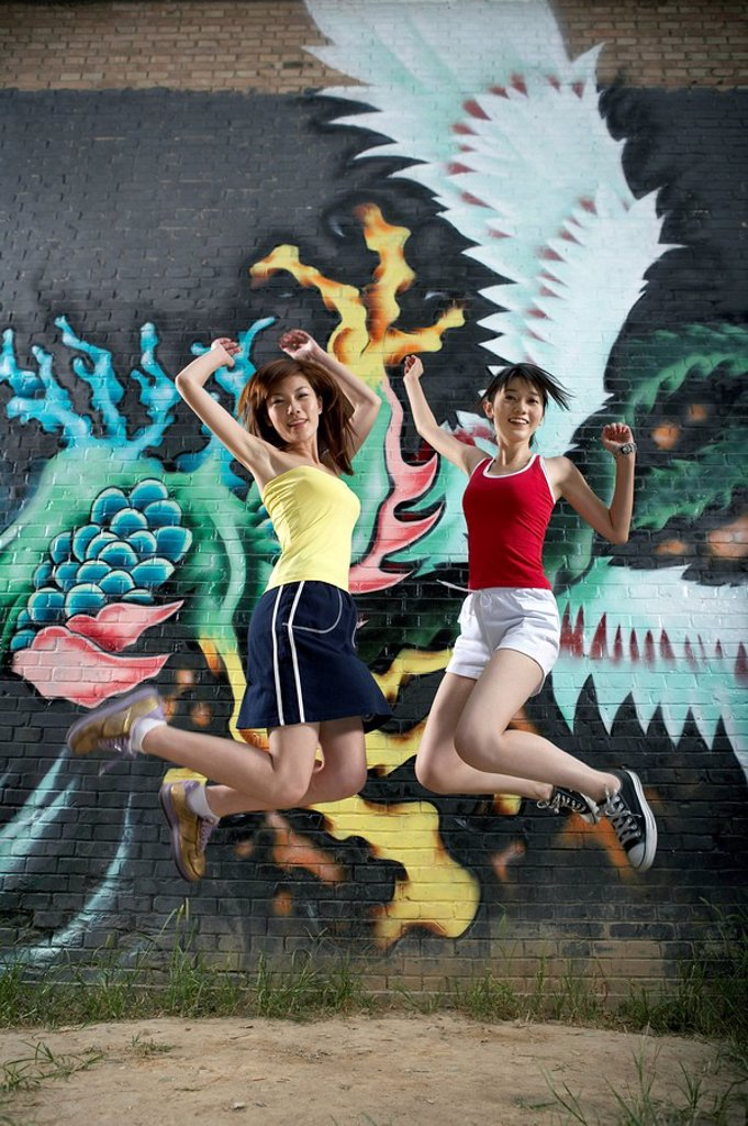 Stock Photo: 1839R-4525 Teenage Girls Jumping Next To Spray Painted Mural