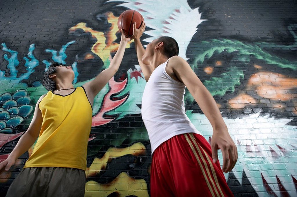 Teenage Boys Playing Basketball Next To Spray Painted Mural : Stock Photo