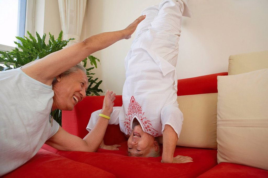 Stock Photo: 1839R-4620 Woman Doing Headstand On Couch