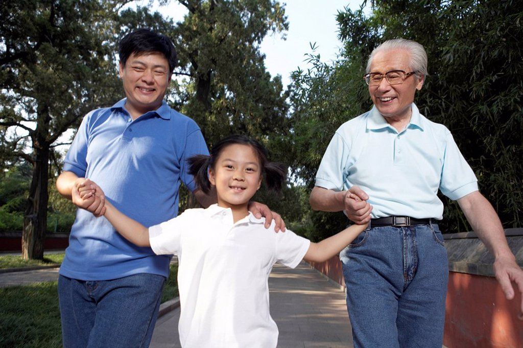 Little Girl Walking With Father And Grandfather Through The Park : Stock Photo