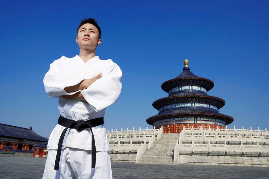 Portrait Of Young Male Martial Artist In Front Of Temple : Stock Photo