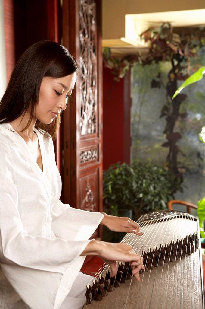 Stock Photo: 1839R-4977 Young Woman Playing Traditional Chinese Instrument