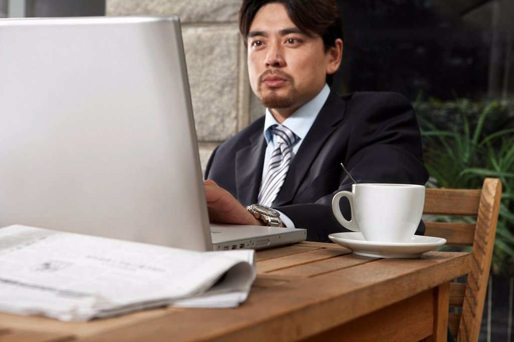 Stock Photo: 1839R-5053 Businessman Using Laptop At Cafe