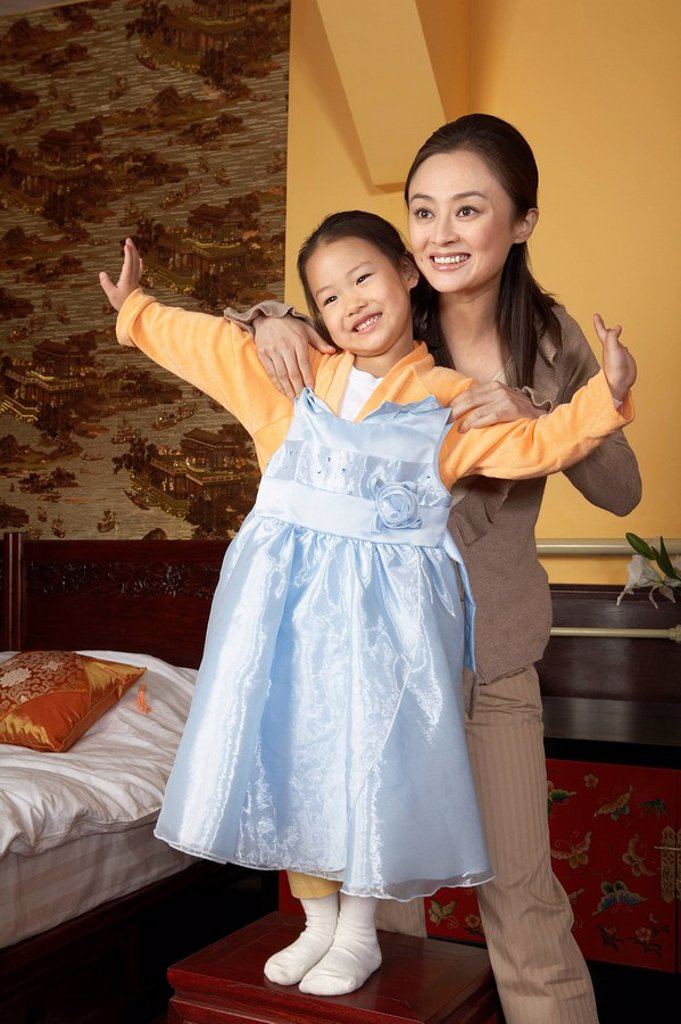 Stock Photo: 1839R-5113 Mother And Daughter Trying On A Dress
