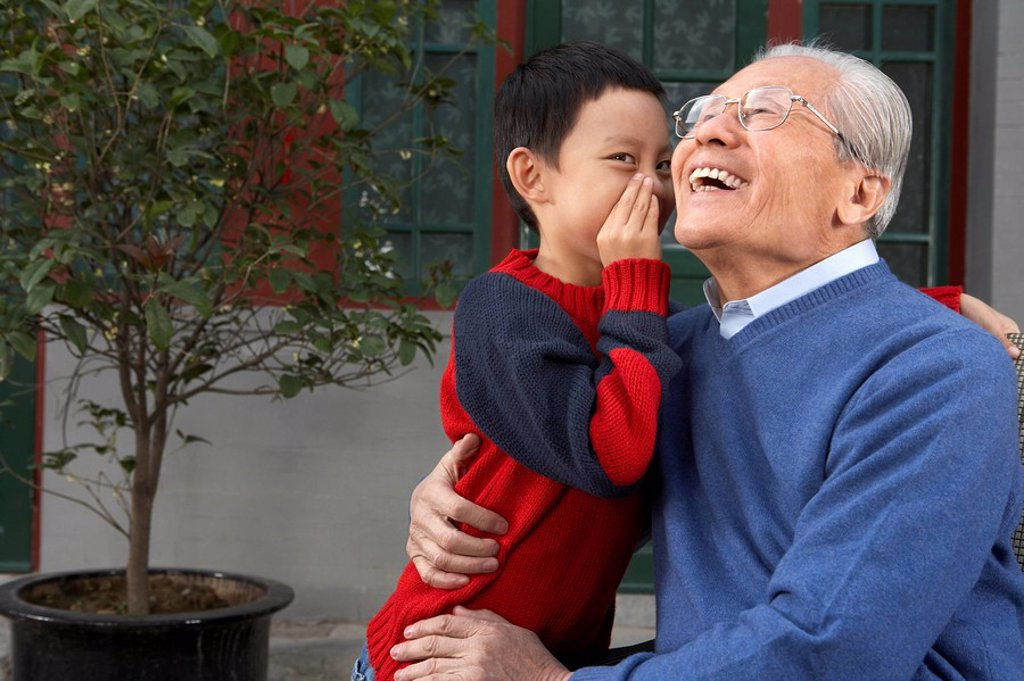 Young Boy Whispering Into Grandfather´ Ear : Stock Photo