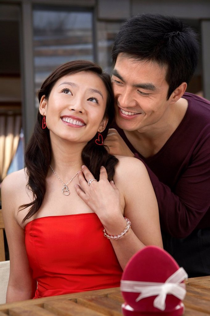 Stock Photo: 1839R-5189 Young Man Putting Necklace On Girlfriend