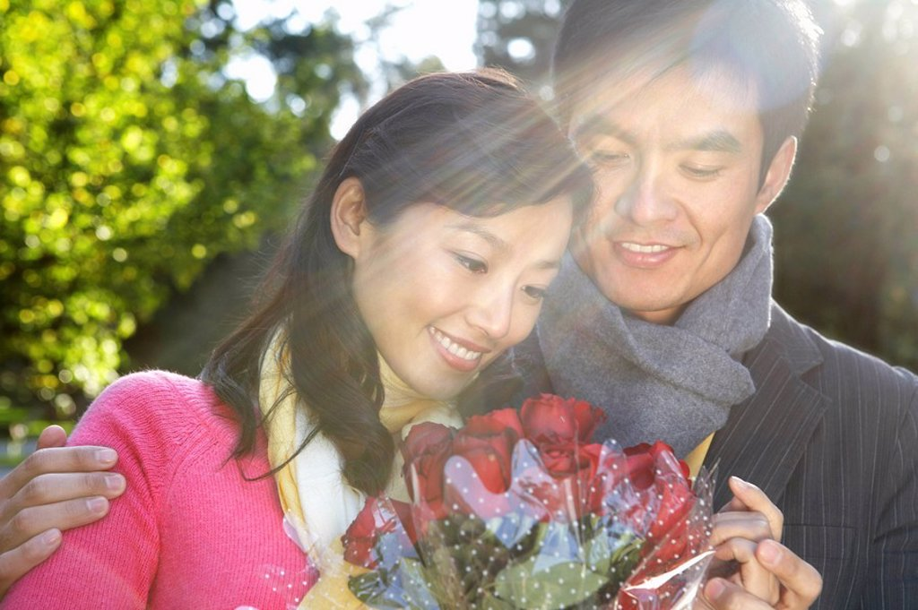 Young Man Giving Flowers To Girlfriend : Stock Photo