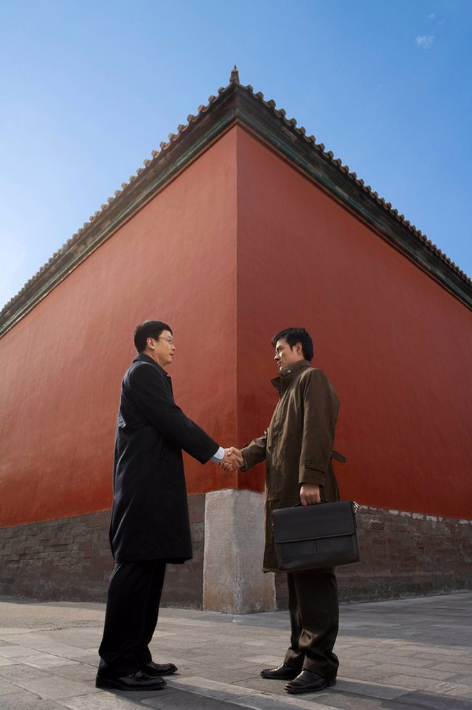 Stock Photo: 1839R-5325 Businessmen Shaking Hands Standing Next To Architectural Structure,