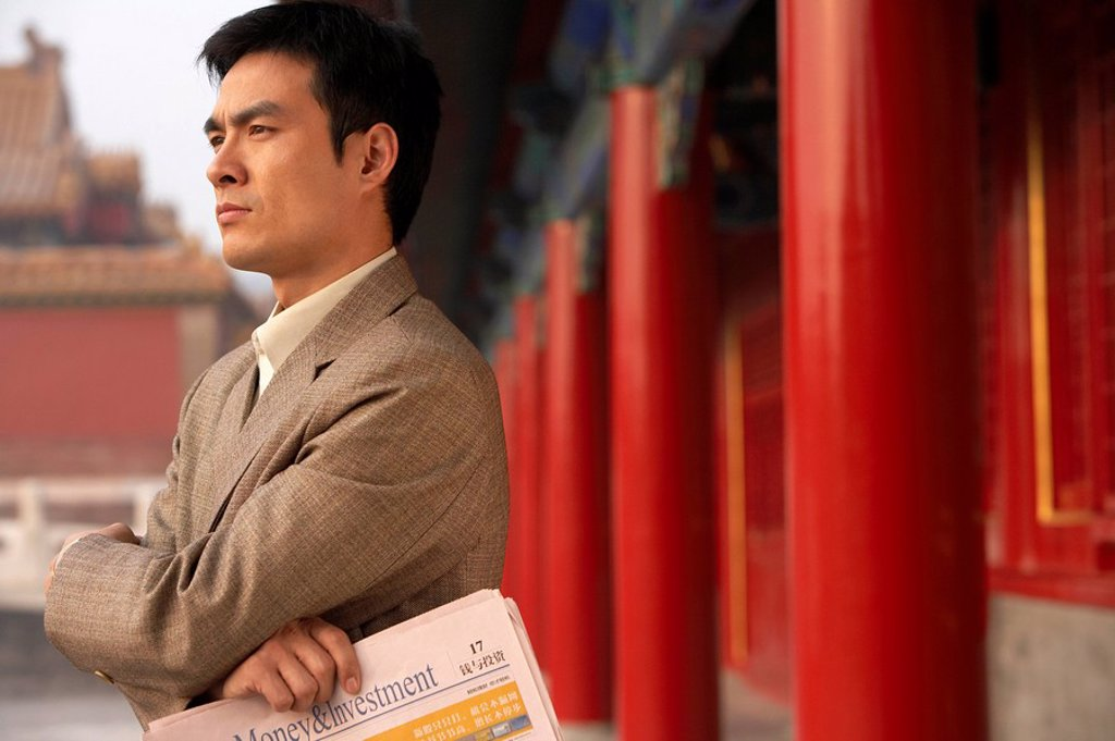 Stock Photo: 1839R-5379 Businessman Holding Newspaper And Standing At The Forbidden City