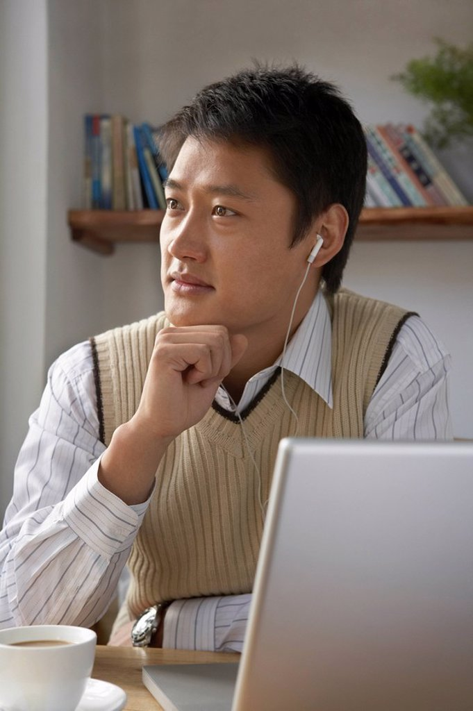 Stock Photo: 1839R-5406 Man Using Laptop Computer With Headphones On